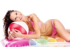 Ragazza in bikini con la sfera sul materasso di aria immagine stock libera da diritti