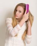 Ragazza bionda abbastanza giovane che spazzola i suoi capelli Fotografia Stock Libera da Diritti