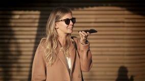 Ragazza bionda allegra in cappotto ed occhiali da sole che parla sul telefono in via di autunno video d archivio