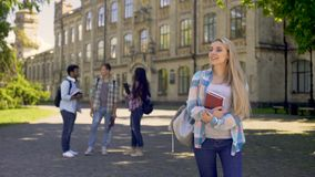 Ragazza bionda allegra che sta a partire dai suoi compagni di classe, ragazzo aspettante stock footage