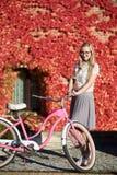 Ragazza bionda attraente alla bicicletta di signora rosa il giorno soleggiato sulla parete invasa con il fondo rosso dell'edera immagine stock