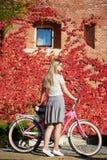 Ragazza bionda attraente alla bicicletta di signora rosa il giorno soleggiato sulla parete invasa con il fondo rosso dell'edera fotografia stock
