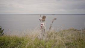 Ragazza bionda attraente in bello vestito bianco lungo da estate con ricamo che balla e che fila intorno sull'erba E video d archivio