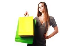 Ragazza bionda attraente con i sacchetti di acquisto isolati Fotografia Stock