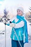 Ragazza bionda attraente con un sorriso con i pali di sci in mani immagine stock libera da diritti