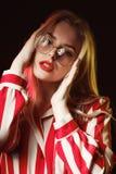 Ragazza bionda attraente in vetri che portano blusa a strisce, posante Immagine Stock