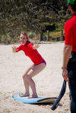 Ragazza bionda che impara praticare il surfing sulla spiaggia Fotografia Stock Libera da Diritti