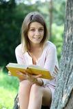 Ragazza bionda che legge un libro nel parco Immagini Stock Libere da Diritti