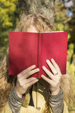 Ragazza bionda che legge un libro in un parco un giorno soleggiato Immagine Stock