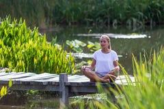 Ragazza bionda che medita, ambiente di zen 20s dello stagno Immagini Stock