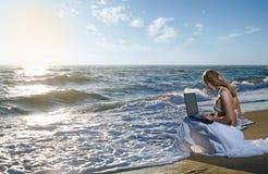 Ragazza bionda che per mezzo del computer portatile sul mare Fotografie Stock