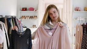 Ragazza bionda che sceglie blusa nera e beige sui ganci che li confrontano davanti ad uno specchio che decidono che cosa comprare stock footage