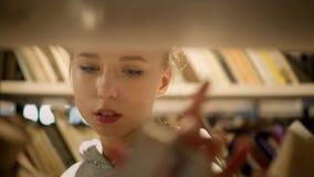 Ragazza bionda che sceglie un libro sullo scaffale nella biblioteca archivi video