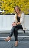 Ragazza bionda che si siede sul banco Fotografie Stock