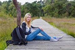 Ragazza bionda che si siede sul percorso di legno in natura Fotografie Stock