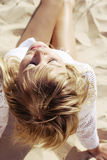 Ragazza bionda che si siede sulla sabbia Immagine Stock Libera da Diritti