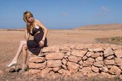 Ragazza bionda che si siede in una parete di pietra Immagine Stock Libera da Diritti