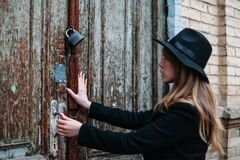 Ragazza bionda con capelli lunghi, in cappotto nero in cappello, provante ad aprire una porta bloccata di vecchia casa con matton fotografia stock