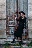 Ragazza bionda con capelli lunghi, in cappotto nero in cappello, supporti sui precedenti di vecchia casa con mattoni a vista dell immagini stock libere da diritti