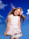 Ragazza bionda con i capelli di salto del vestito da modo in cielo blu Fotografie Stock