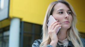 Ragazza bionda con i colloqui lunghi dei capelli sul telefono mentre cammina lungo la via Fine sul ritratto, stile di vita, urban video d archivio