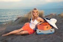 Ragazza bionda con i suoi bagagli sulla spiaggia Fotografie Stock Libere da Diritti