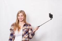 Ragazza bionda con il bastone del selfie Fotografia Stock