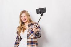 Ragazza bionda con il bastone del selfie Fotografia Stock Libera da Diritti
