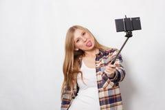 Ragazza bionda con il bastone del selfie Immagine Stock
