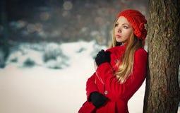 Ragazza bionda con il cappotto rosso nella neve di inverno fotografie stock
