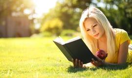 Ragazza bionda con il libro e Apple su erba verde Bella donna Immagini Stock