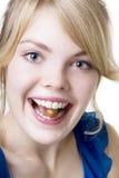 Ragazza bionda con la noce in vostri denti Immagini Stock Libere da Diritti