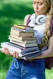 Ragazza bionda con le cuffie che tengono mucchio dei libri in parco Fotografie Stock