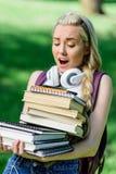 Ragazza bionda con le cuffie che tengono mucchio dei libri in parco Fotografia Stock Libera da Diritti