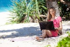 Ragazza bionda con un computer portatile sulla spiaggia tropicale Fotografie Stock
