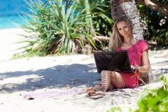 Ragazza bionda con un computer portatile sulla spiaggia tropicale Fotografia Stock