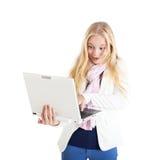 Ritratto di una ragazza bionda sorpresa con un computer portatile. Fotografia Stock Libera da Diritti