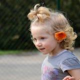 Ragazza bionda con un fiore arancio in capelli Immagine Stock