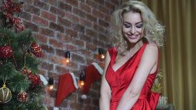 Ragazza bionda con uno sguardo fisso seducente che flirta vicino ad un albero di Natale video d archivio