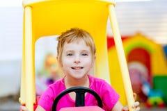 Ragazza bionda dei bambini che conduce l'automobile del giocattolo Fotografie Stock