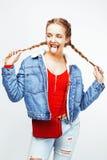 Ragazza bionda dei pantaloni a vita bassa abbastanza alla moda dei giovani con la posa delle trecce emozionale isolata sul sorrid Fotografia Stock