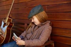 Ragazza bionda del bambino che gioca il berretto di inverno dello smartphone Fotografia Stock Libera da Diritti
