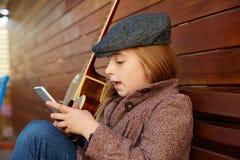 Ragazza bionda del bambino che gioca il berretto di inverno dello smartphone Fotografia Stock
