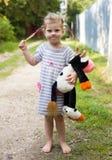 Ragazza bionda del bambino nei piedi nudi del vestito da estate con il giocattolo della mucca Fotografie Stock Libere da Diritti