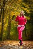 Ragazza bionda della donna adatta di forma fisica che fa esercizio in parco autunnale. Sport. Immagine Stock Libera da Diritti