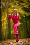 Ragazza bionda della donna adatta di forma fisica che fa esercizio in parco autunnale. Sport. Immagini Stock