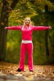 Ragazza bionda della donna adatta di forma fisica che fa esercizio in parco autunnale sport Fotografia Stock Libera da Diritti