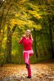 Ragazza bionda della donna adatta di forma fisica che fa esercizio in parco autunnale sport Immagine Stock Libera da Diritti