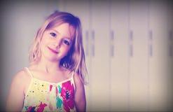 Ragazza bionda di sei anni in un vestito bianco da estate con i fiori che sorride su un fondo astratto con effetto di nebbia blu fotografia stock