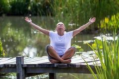 Ragazza bionda di zen 20s che gode dell'aria fresca, ambiente dello stagno Immagine Stock Libera da Diritti